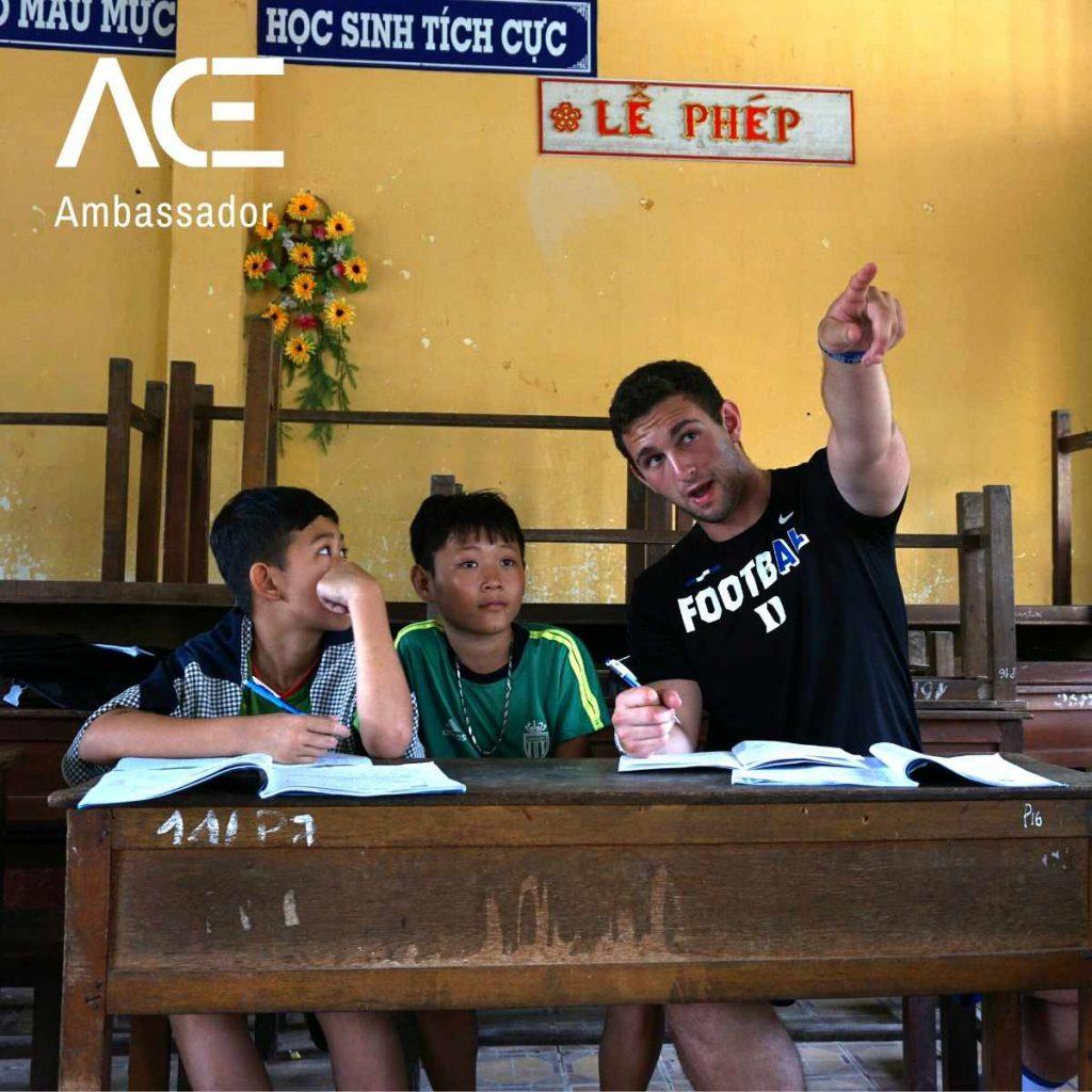 man teaching two children at a desk