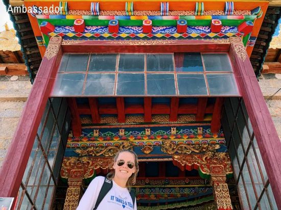 woman posing in front of colorful architecture