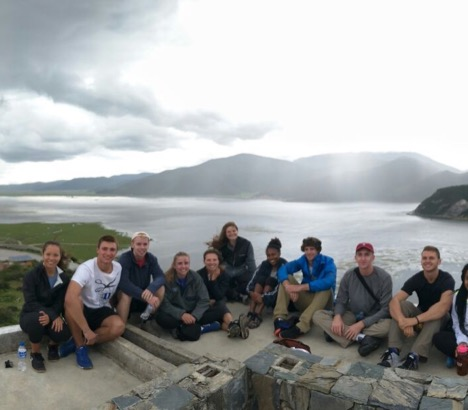 group of young student-athletes sitting in front of mountainous overlook