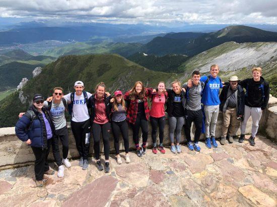 group posing above mountainous overlook
