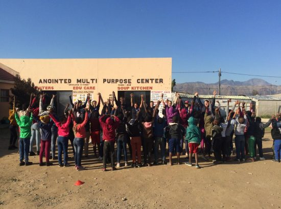 group of kids outside school building raising hands