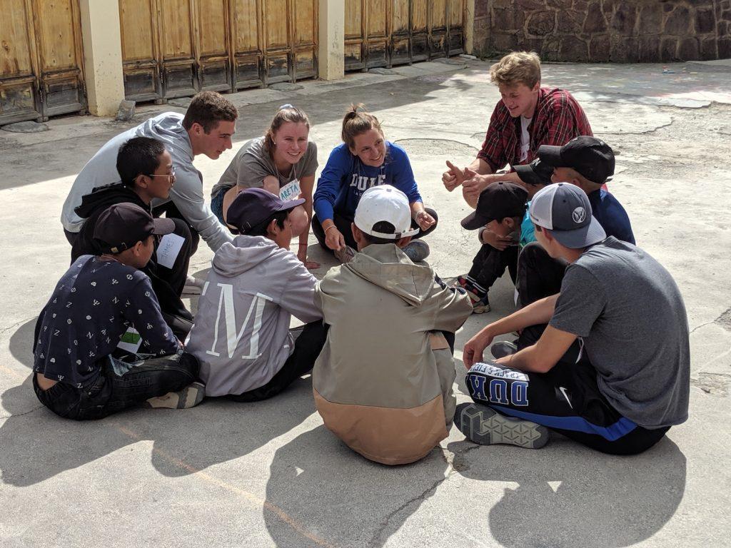 group sitting outside huddling on basketball court