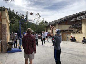 person shooting basketball outside