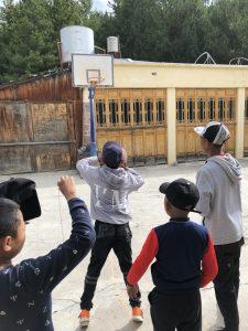 group of children shooting basketball outside