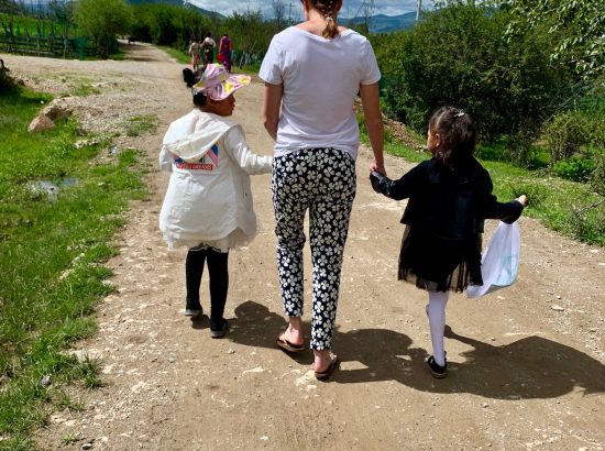 young adult walking and holding hands with two children outside