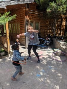 young adult hula hooping while child watches