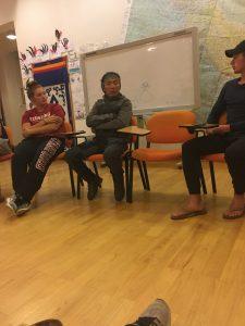three men talking in front of classroom