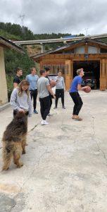 group of young adults shooting basketball outside