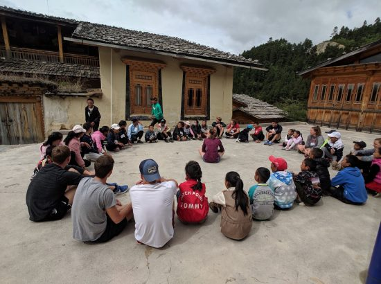 group of kids and young adults sitting in a circle outside