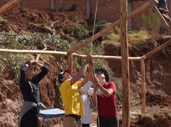 group of young people building wooden structure outside