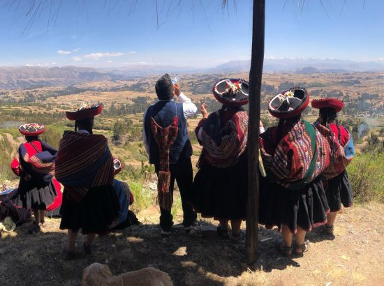people wearing traditional colorful clothing and hats facing outward looking at overlook