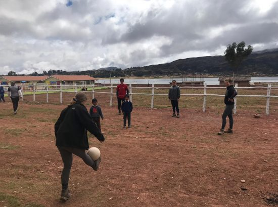 student playing soccer outside with kids
