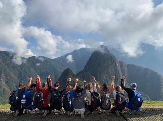 group photo of students linking arms looking at mountain