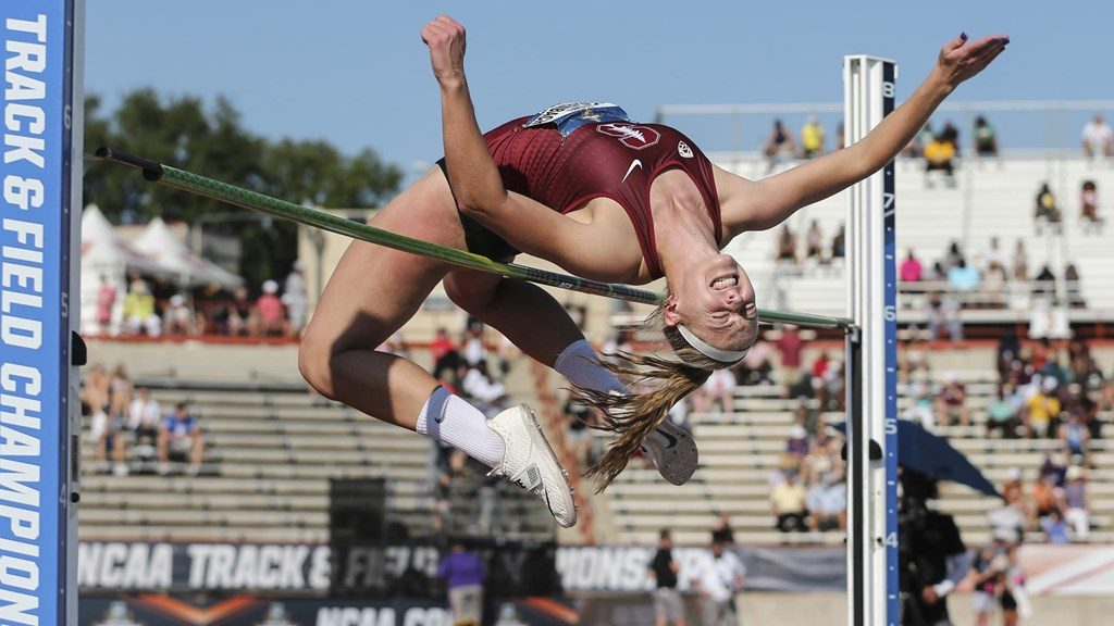 young woman jumping over high hurdle
