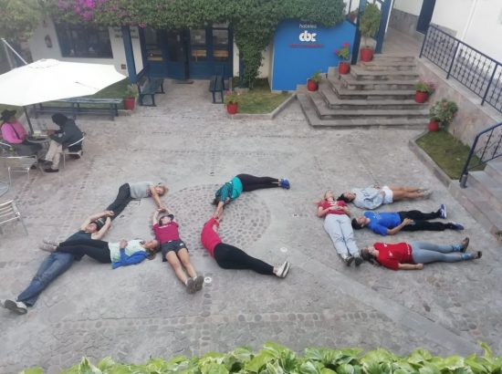 """students lying down on the ground to form the word """"ACE"""""""