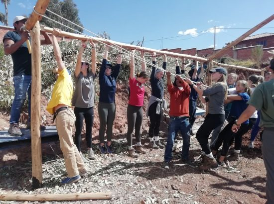 students holding up a pole at a constrution site