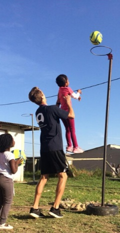 boy lifting a small child up to a make a net ball dunk