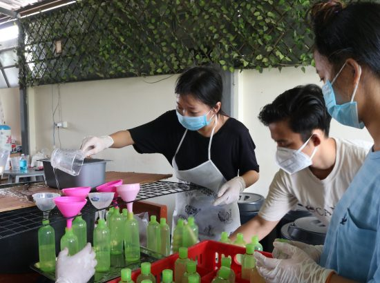people wearing masks filling up soap bottles using funnel
