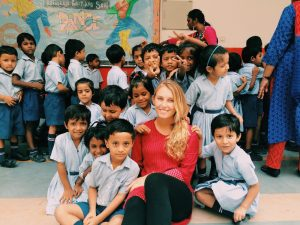 woman hugging many schoolchildren