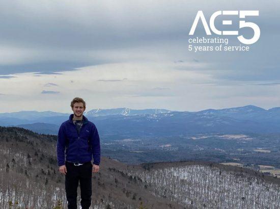 man standing in front of snowy mountainous overlook