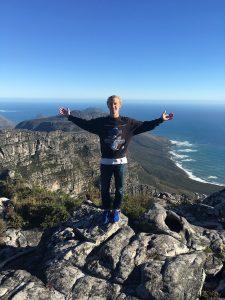 man man standing in front of beachy mountainous overlook