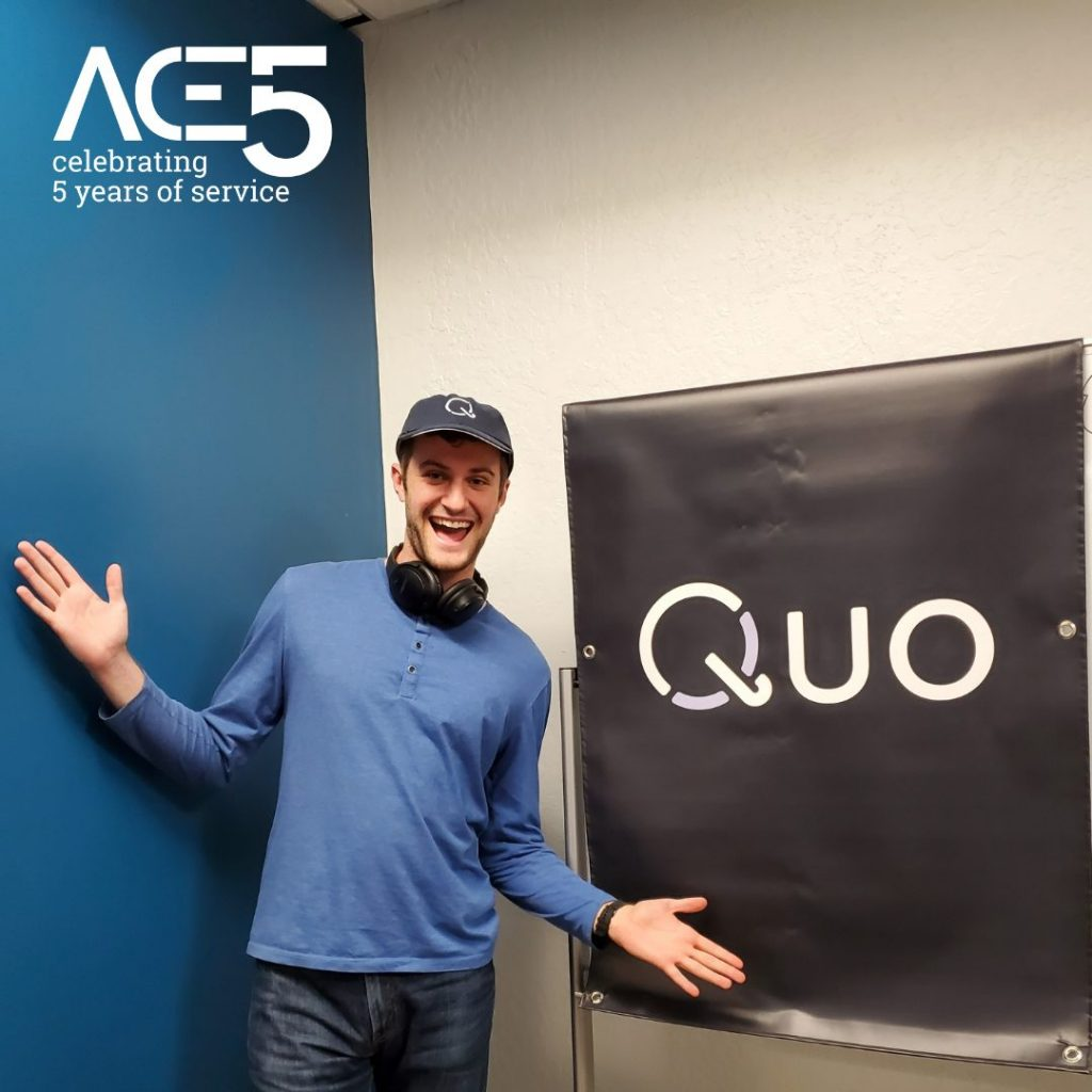 """man posing in front of sign that says """"quo"""""""
