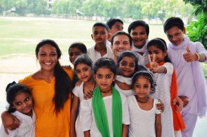 group of schoolchildren smiling with teacher outside