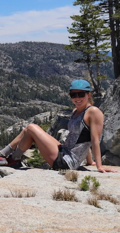 woman sitting on rock on top of mountain