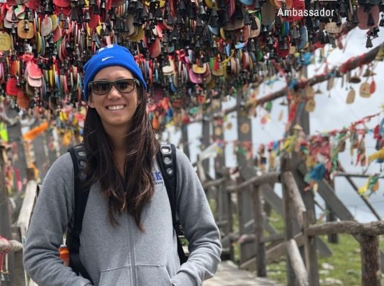 woman smiling in front of many locks that are locked on to a bridge