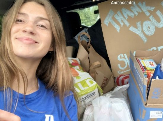 woman next to bags of food and large box