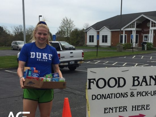 woman donating food in front of food bank