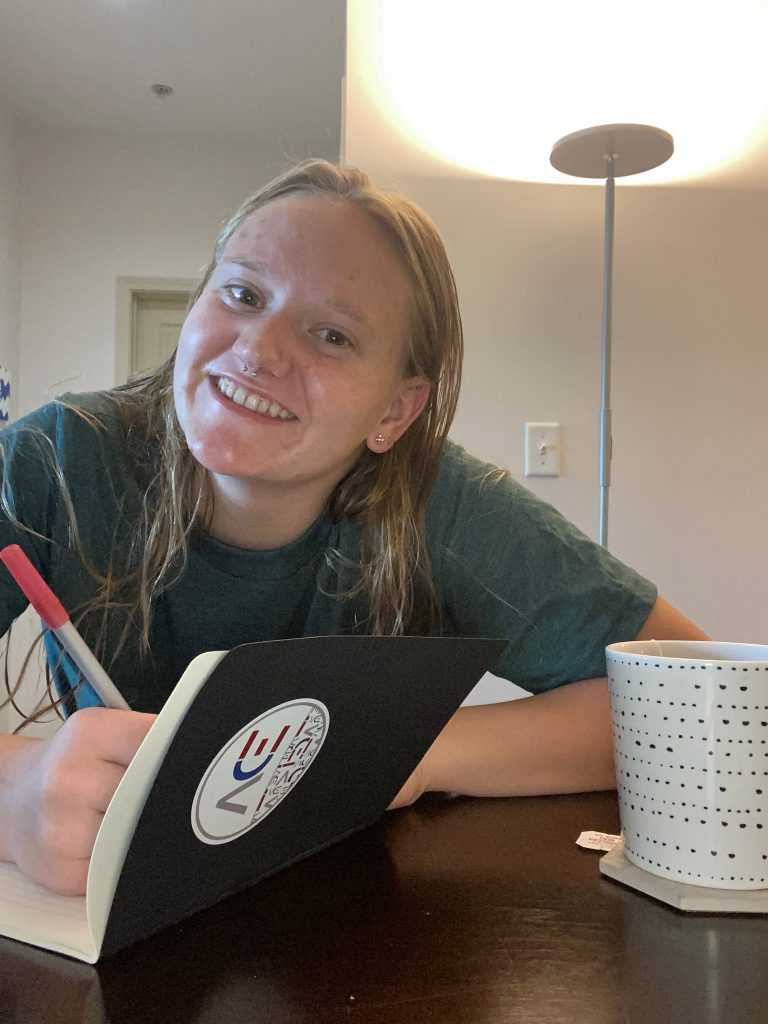 woman smiling while journaling